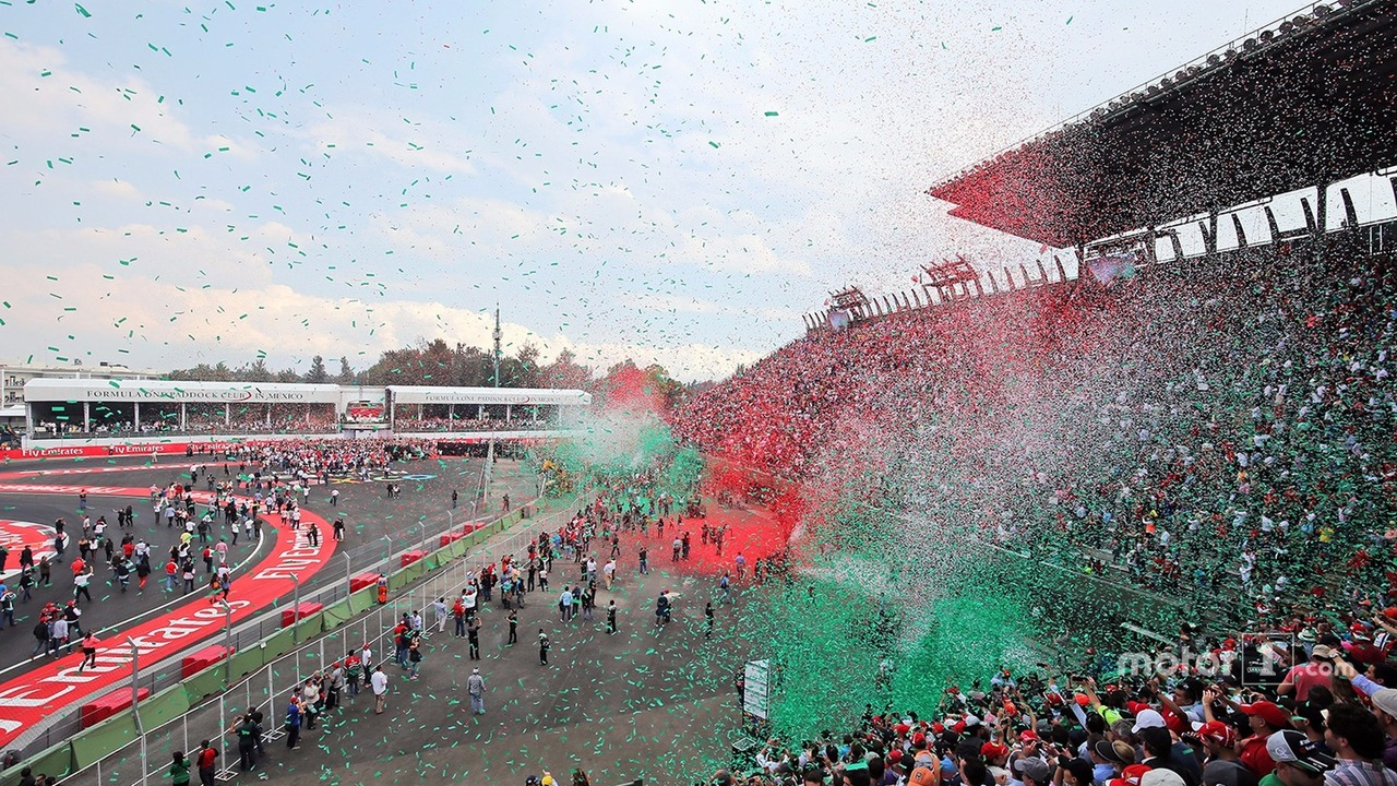 Ticker tape covers fans in the grandstand as the podium takes place