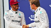 Lewis Hamilton celebrates his pole position with third placed team mate Nico Rosberg in parc ferme
